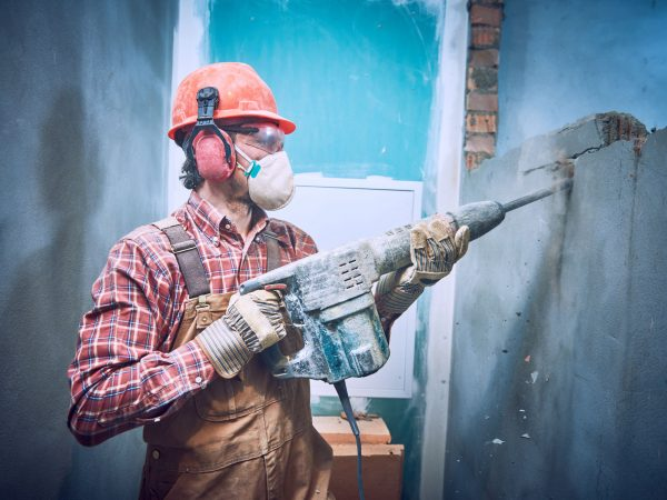 Worker in personal protection equipment with demolition hammer at interior brick wall construction breaking in building industry