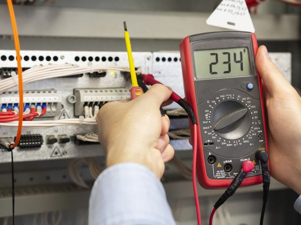 Electrician measurements with multimeter tester. Male Technician Examining Fusebox With Multimeter Probe. Closeup of multimeter in hands of engineer